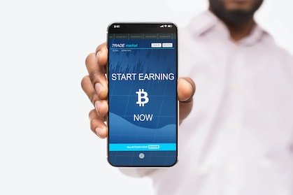 "middle aged and black crypto investor holding a smartphone saying ""start earning bitcoin today"""