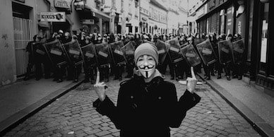 Anonymous rebel showing fingers to the authorities in the street