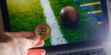 middle aged crypto investor holding a bitcoin coin in front of a laptop expressing that betting with crypto on sports is possible